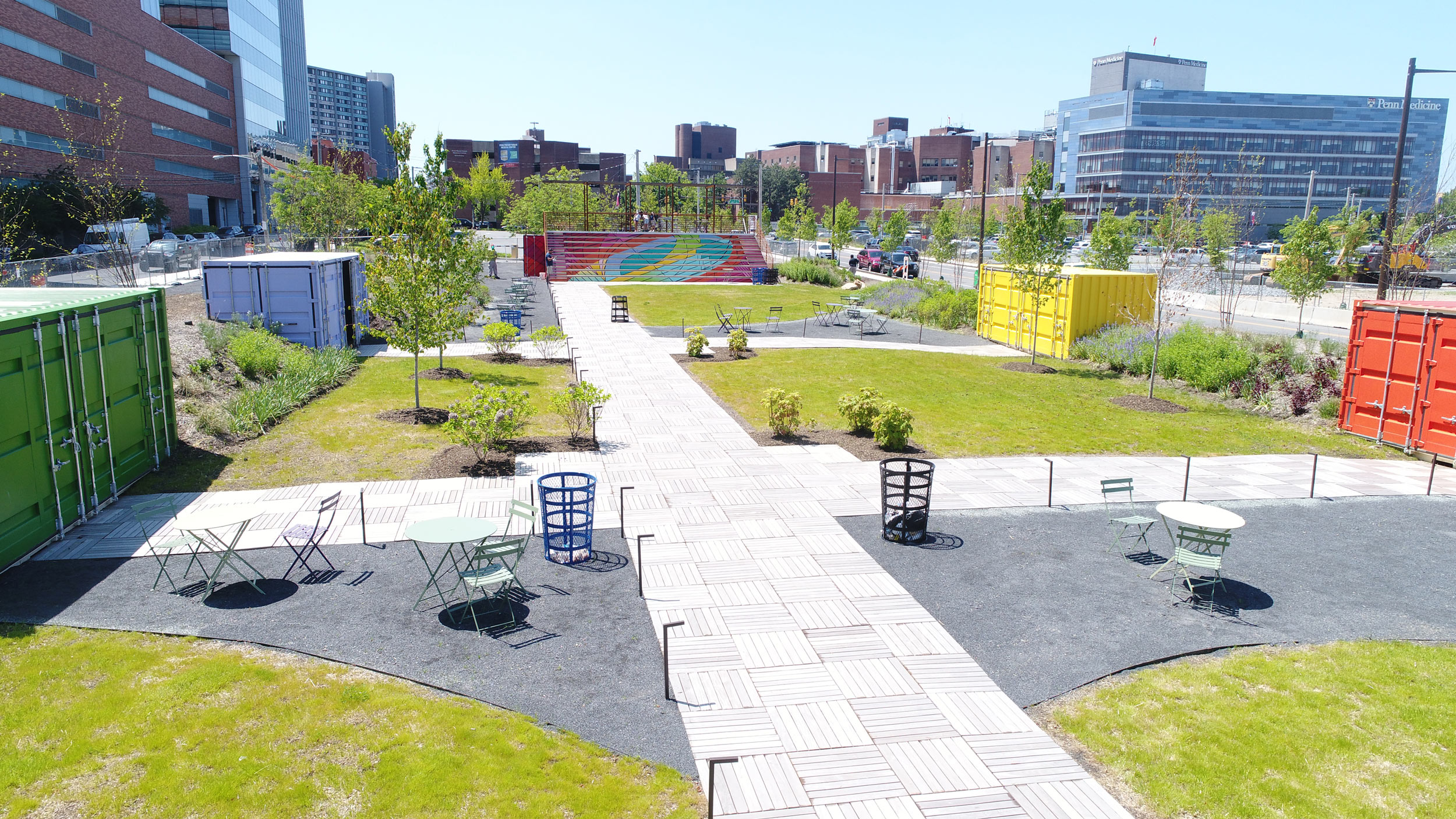 Green City works installed The Lawn at U city Square: including mature tree and shrub species, perennials plantings built on earthen berms, four decomposed granite, permeable seating areas, a linear Ipe boardwalk, and path lighting.