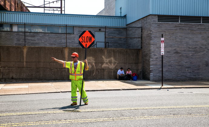 A construction worker holds a sign that reads 'slow'