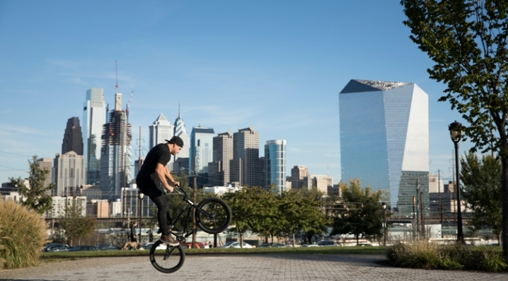 A bike rider performs a trick in front of the skyline